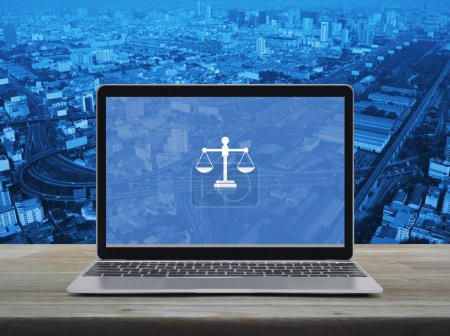 Photo for Law flat icon with modern laptop computer on wooden table over city tower, street, expressway and skyscraper, Business legal service online concept - Royalty Free Image