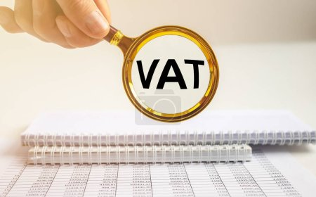 Photo pour Texte TVA, Taxe sur la valeur ajoutée, inscription par loupe sur table de bureau. - image libre de droit