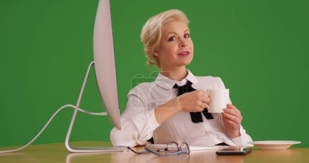 Confident white businesswoman with coffee sitting at desk on green screen