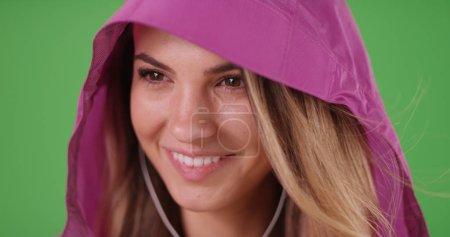 Closeup of pretty woman in rain jacket listening to music on green screen