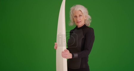 Mature white female surfer posing with surfboard on green screen
