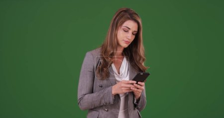 Businesswoman using smartphone to communicate with client on green screen