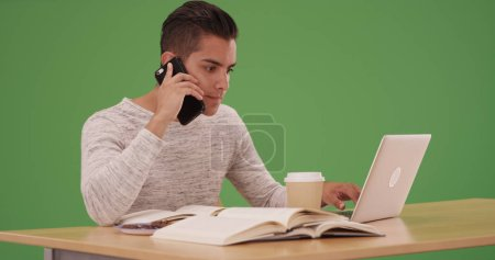 Millennial Latino university student with laptop and cellphone on green screen