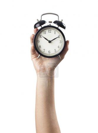 Photo pour La main de la femme sur fond blanc isolée par un réveil - image libre de droit
