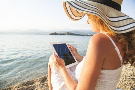 Girl with digital tablet near beach