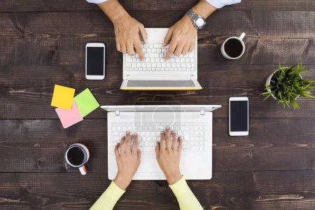 Photo pour Les gens d'affaires travaillant dans le bureau, ils utilisent l'ordinateur portable, vue supérieure - image libre de droit