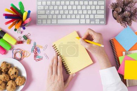 Photo pour Femme prenant des notes pour prendre des notes sur une table de bureau. Table rose, vue de dessus. Conception à plat. - image libre de droit