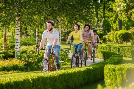 Photo for Happy friends cycling in city park. Group of students riding bikes on summer nature background. People and active rest. - Royalty Free Image