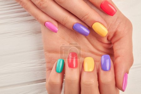 Photo for Woman hands with multicolored nail polish. Close up of female hands with beautiful summer manicure. Concept of nail treatment and spa. - Royalty Free Image