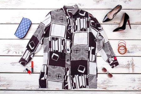 Photo pour Pose plate, accessoires féminins et chemise élégante. Vue de dessus, vêtements femme d'été. Fond en bois blanc . - image libre de droit