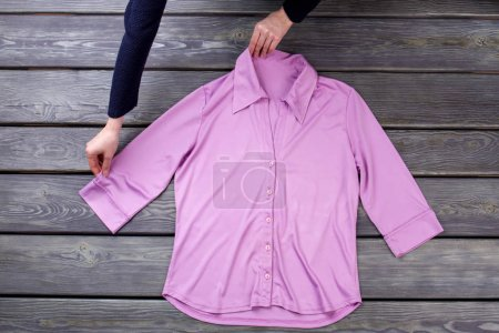 Photo for Top view women dispose pink shirt. Grey wooden surface background. - Royalty Free Image