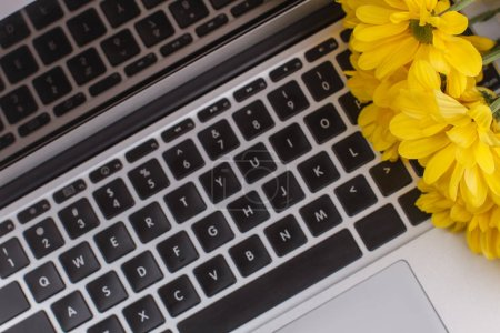 Laptop keyboard and yellow flowers close up.