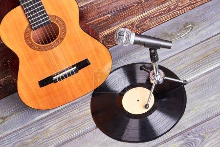 Photo pour Guitare, vinyle et microphone. Instruments de musique Vintage sur fond en bois. - image libre de droit