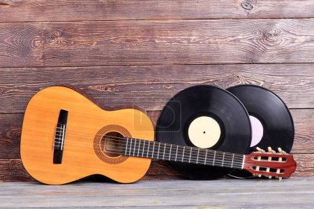 Photo for Acoustic guitar and vinyl records. Musical instuments on wooden background. Vintage musical background. - Royalty Free Image