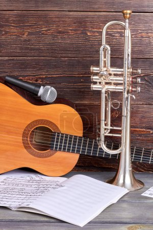 Photo for Vintage musical instruments on wooden background. Guitar with microphone, trumpet and musical notes. Professional musical equipment. - Royalty Free Image