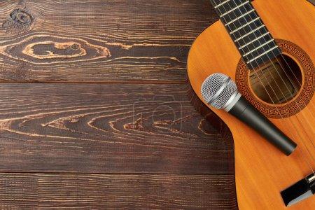 Guitarra acústica con micrófono sobre fondo de madera. Guitarra clásica con micrófono sobre mesa de madera marrón con espacio para copiar. Fondo de equipo musical .