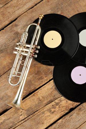Photo pour Trompette et vinyl records sur des planches en bois. Plaques de vinyle et de la trompette sur plancher en bois rustique, vue de dessus. - image libre de droit