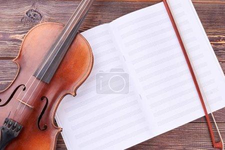 Photo pour Violon, archet et notes de musique. Brun violon et archet sur feuilles musicales. Classique équipement d'orchestre. - image libre de droit