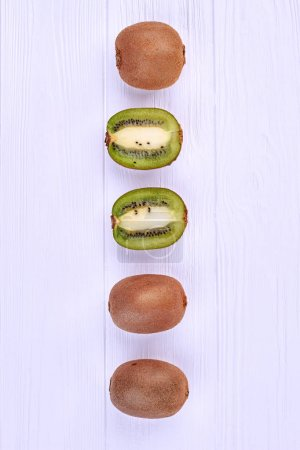 Photo for Row of whole and sliced kiwi fruits. Ripe kiwi fruits on white wooden background, top view. - Royalty Free Image