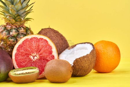 Photo for Summer composition from fresh exotic fruits. Whole and cut tropical fruits on yellow background. - Royalty Free Image