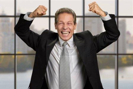 Photo pour Homme d'affaires extatique avec les poings surélevés. Heureux homme d'affaires d'âge moyen, célébrant les succès de l'entreprise sur fond de fenêtre de bureau. - image libre de droit
