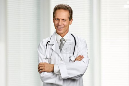 Photo for Portrait of cheerful doctor with crossed arms. Smiling male doctor with stethoscope folded arms on blurred background. People, occupation, healthcare. - Royalty Free Image