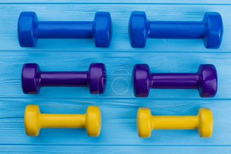 Photo for Collection of colorful dumbbells on wooden background. Group of multicolored hand weights. Sport and fitness concept. - Royalty Free Image