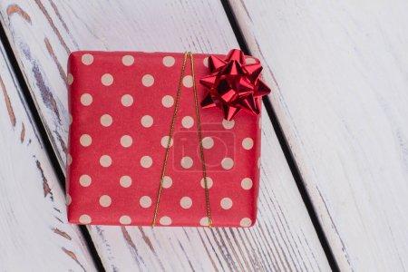 Photo pour Cadeau de Noël enveloppés dans du papier rouge en pointillés. Boîte présente enveloppé dans papier à motifs et liée avec le ruban d'or. Cadeau pour elle. - image libre de droit