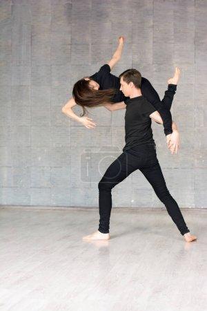Photo pour Jeune couple dansant en pose dynamique. Talentueux garçon et fille portant des vêtements noirs dansant la danse moderne sur fond gris . - image libre de droit