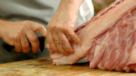 Photo pour Gros plan des mains de bouchers couper le porc en magasin boucherie-charcuterie. Viande fraîche à la boucherie. Production de viande saine à l'usine. - image libre de droit