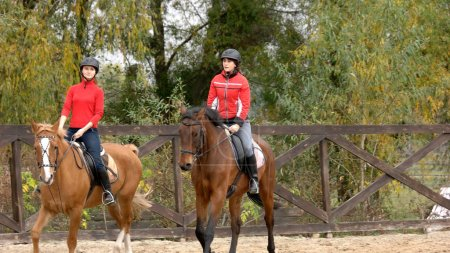 Photo for Two young women riding horses. Two girls equestrians in helmets riding horses on training ground, front view. People, leisure, animals, active lifestyle. - Royalty Free Image