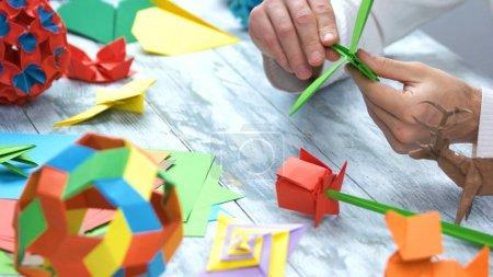 Photo pour Grue de papier de fabrication à l'atelier. Leçons d'origami, origami art. Belle activité loisirs et amusement. - image libre de droit