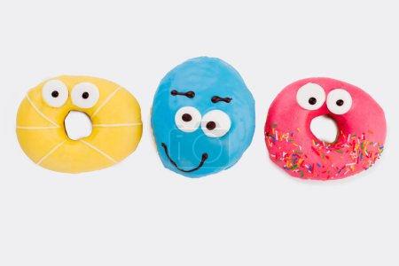 Photo for Three funny donuts on white background. Row of donuts with colorful icing. Yummy glazed dessert. - Royalty Free Image