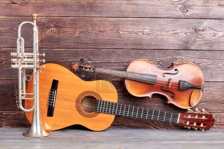 Photo for Musical instruments of vintage style. Trumpet, acoustic guitar and violin on wooden background. Classical musical instruments. - Royalty Free Image