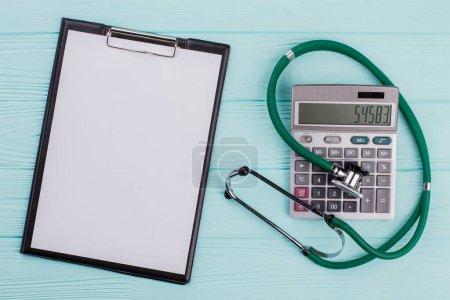 Photo pour Le coût conceptuel des soins de santé se compose d'une calculatrice stéthoscopique. Presse-papiers vide sur le côté gauche. - image libre de droit