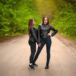 Two confident girls posing on rural road. Girls in...