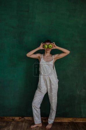 Photo pour Jeune femme en costume blanc posant et la tenue des pommes sur fond de mur végétalisé - image libre de droit