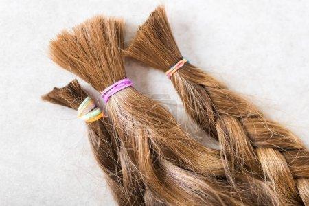 Photo pour Couper de beaux cheveux longs comme des dons de charité des enfants, qui rend les perruques pour les patients atteints de cancer, fond clair - image libre de droit
