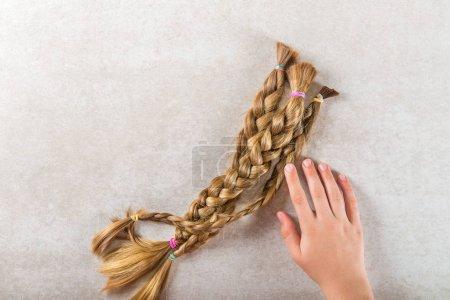 Photo pour Main tient les cheveux longs comme des dons de charité des enfants, qui rend les perruques pour les patients atteints de cancer, fond clair - image libre de droit