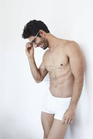 Man in Glasses and underwear smiling and looking down