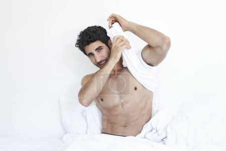 Undressing man in bed, looking to camera
