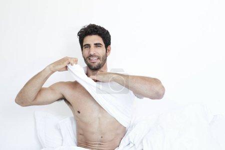Man undressing in bed, portrait