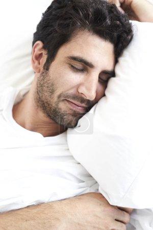 Restful man sleeping in bed