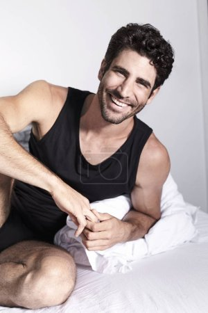 Smiling guy in underwear on bed, portrait