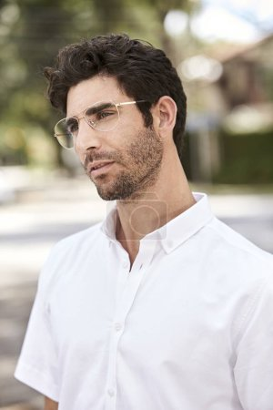 Thoughtful man in glasses looking away
