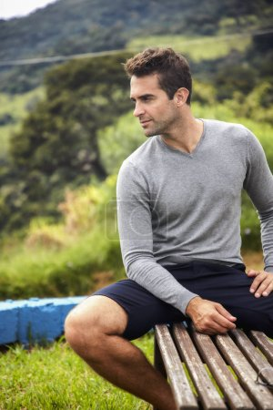 Photo for Handsome man in shorts, sitting on bench - Royalty Free Image