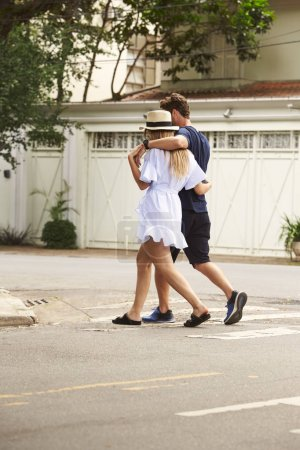 Photo pour Jeune couple traversant la rue ensemble - image libre de droit