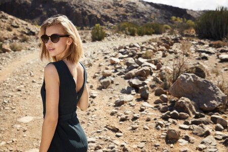 Beautiful young woman in green dress in desert