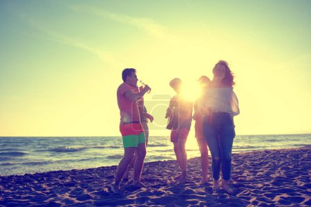 Photo pour Groupe de jeunes gens heureux dansant à la plage sur le beau coucher de soleil d'été - image libre de droit