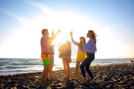 Photo for Group of happy young people dancing at the beach on beautiful summer sunset - Royalty Free Image